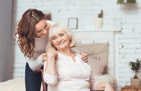 Angehöriger pflegt Seniorin im Rollstuhl