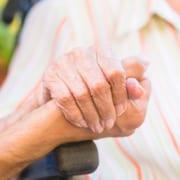 Pflegerin berührt Hand des Patienten