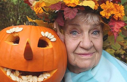 Seniorin mit Halloween-Kürbis