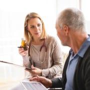 Pfleger erklärt Senioren die Medikamenteneinnahme