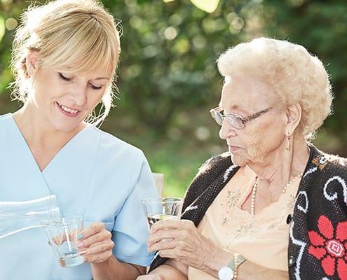 Pflegekraft bezieht Seniorin aktivierend mit ein