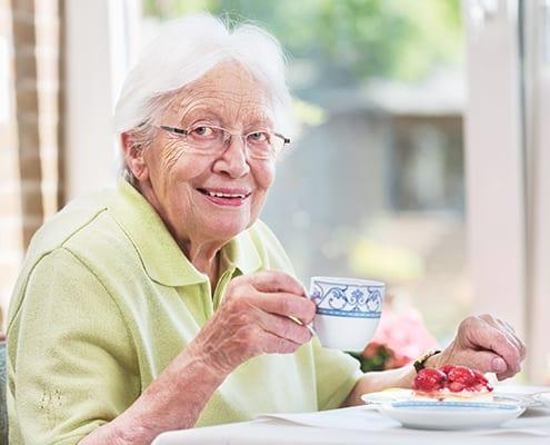 Senioren in häuslicher Altenpflege trinkt Kaffee