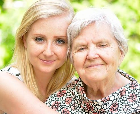 Seniorin mit herzlicher Pflegekraft
