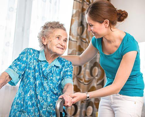 Frau bei der Pflege einer Angehörigen zu Hause