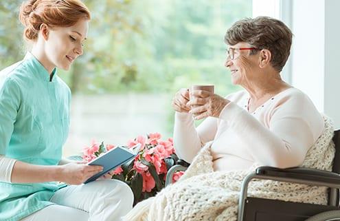 24-Stunden-Pflegekraft liest Seniorin vor