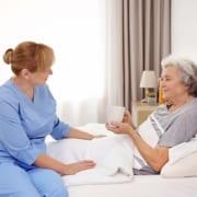 häusliche Pflegehilfe bringt Seniorin Tee