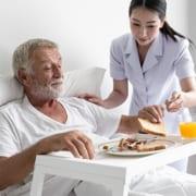Senior wird von Pflegekraft zu Hause versorgt