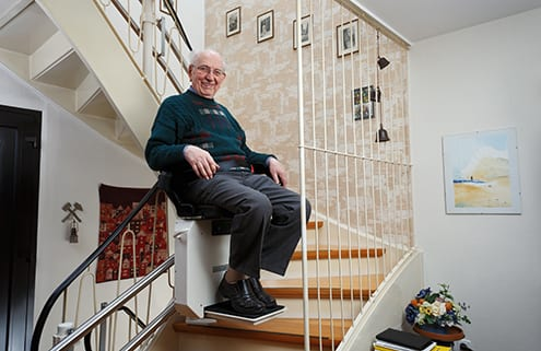 Senior mit kostengünstigem Treppenlift dank Preisvergleich