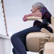Seniorin nutzt Treppenlift auf schmaler Treppe